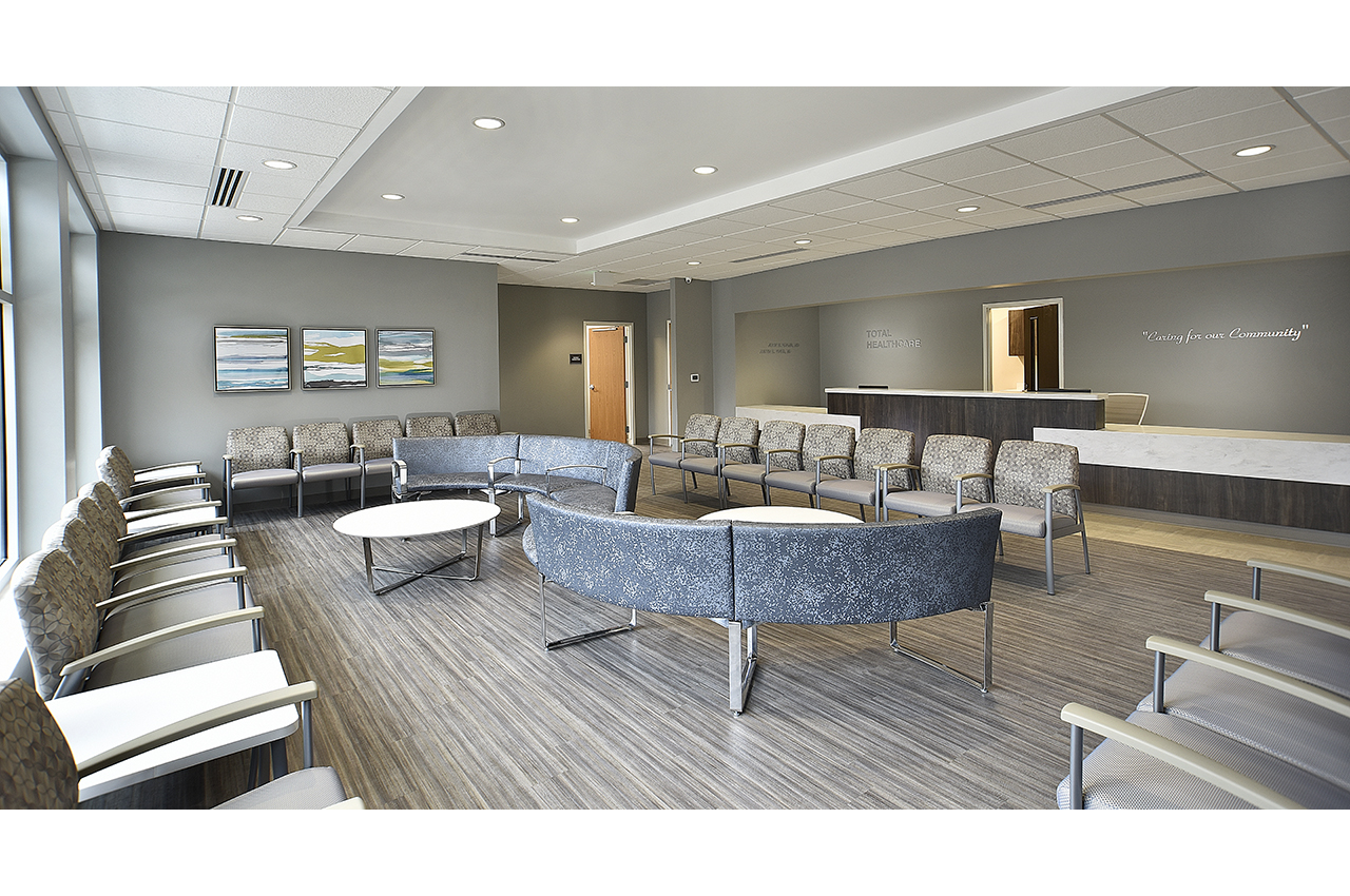 total healthcare waiting room at russell medical center including curved lounge seating, colorful artwork, and timeless wood textures